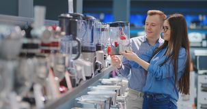 年轻夫妇男人和妇女电器商店的为他们的厨房选择一台搅拌器 股票视频