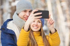 年轻夫妇画象在的明亮的衣裳在一个森林里做一selfie在冬天 库存图片