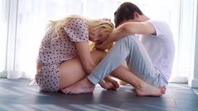年轻夫妇的沮丧的早晨坐与下来头的地板 股票录像