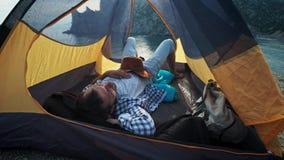 年轻夫妇的腿特写镜头视图在有被加入的脚的野营的帐篷的,当休息时在远足天以后 愉快的恋人 股票视频