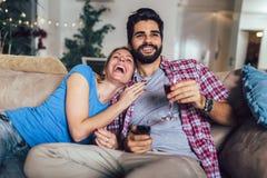 年轻夫妇看着电视在客厅 库存图片