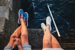 年轻夫妇腿上面接近的视图在运动鞋的坐码头近对海,旅行概念 免版税库存照片