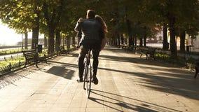 年轻夫妇获得乘坐在同一辆自行车的乐趣在与太阳背后照明的室外活动在背景 坐的女孩  股票视频