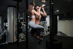 年轻夫妇解决在健身房 可爱的妇女和英俊的肌肉人在轻的现代健身房训练 赤裸上身的人是 免版税图库摄影