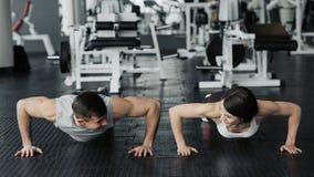 年轻夫妇解决在健身房 可爱的妇女和英俊的肌肉人在轻的现代健身房训练 ?? 库存图片