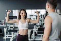 年轻夫妇解决在健身房 可爱的妇女和英俊的肌肉人教练员在轻的现代健身房训练 ?? 免版税图库摄影