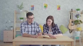 年轻夫妇读书和学习在一栋现代公寓的一本书 股票视频