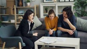 年轻夫妇谈话与看文件和公寓计划的地产商桌 股票视频