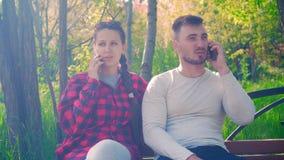 年轻夫妇谈话在电话智能手机 黑色的一个女孩和红色衬衣,一件灰色T恤杉的一个人 股票视频