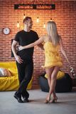 年轻夫妇跳舞的拉丁音乐:Bachata, merengue,辣调味汁 两在咖啡馆的高雅姿势与砖墙 免版税库存图片