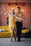 年轻夫妇跳舞的拉丁音乐:Bachata, merengue,辣调味汁 两在咖啡馆的高雅姿势与砖墙 免版税图库摄影