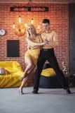 年轻夫妇跳舞的拉丁音乐:Bachata, merengue,辣调味汁 两在咖啡馆的高雅姿势与砖墙 库存照片
