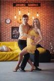 年轻夫妇跳舞的拉丁音乐:Bachata, merengue,辣调味汁 两在咖啡馆的高雅姿势与砖墙 免版税库存照片