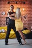 年轻夫妇跳舞的拉丁音乐:Bachata, merengue,辣调味汁 两在咖啡馆的高雅姿势与砖墙 图库摄影