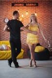 年轻夫妇跳舞的拉丁音乐:Bachata, merengue,辣调味汁 两在咖啡馆的高雅姿势与砖墙 库存图片