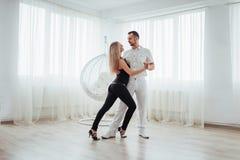年轻夫妇跳舞的拉丁音乐:Bachata, merengue,辣调味汁 两在绝尘室的高雅姿势 免版税库存图片