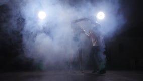 年轻夫妇跳舞的拉丁音乐 Bachata, merengue,辣调味汁 暗室 免版税库存照片