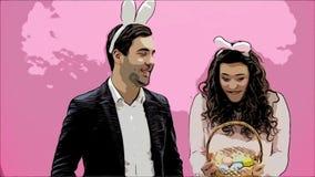 年轻夫妇身分常设在桃红色背景 使用在头的兔宝宝耳朵 在这个人期间给他的妻子一个篮子 股票视频