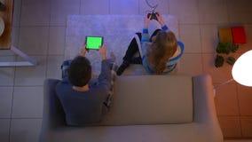 年轻夫妇顶面射击在演奏与控制杆和片剂的睡衣裤的计算机游戏在客厅 股票录像
