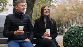年轻夫妇饮用的咖啡和谈话,当坐一条长凳,在街道时 股票视频