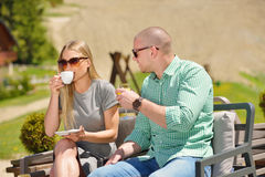 年轻夫妇饮用的咖啡在他们的庭院里在一个美好的夏日 库存图片
