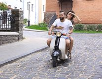 年轻夫妇骑马小型摩托车在城市 免版税图库摄影