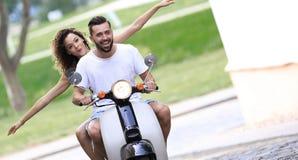 年轻夫妇骑马小型摩托车在城市 库存图片