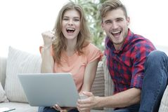 年轻夫妇高兴,坐在开放膝上型计算机前面的长沙发 免版税库存图片