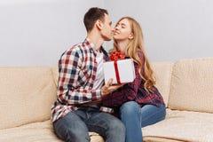 年轻夫妇,一个人给妇女一件礼物,在家坐长沙发 免版税库存照片