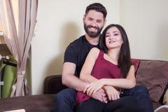 年轻夫妇,拥抱妇女和微笑对照相机的男性 免版税库存照片