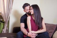 年轻夫妇,拥抱妇女和微笑对照相机的男性 免版税库存图片
