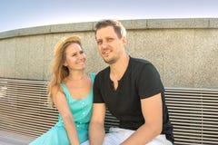 年轻夫妇,男人和妇女,坐在Th的一条长凳 免版税库存图片