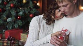 年轻夫妇,男人和妇女,微笑,愉快,佩带的圣诞节装饰,举行新年戏弄 股票录像