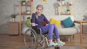 年轻女人一个轮椅的癌症患者在围巾在化疗以后的接受的修复 股票录像