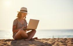 年轻女人与在自然的膝上型计算机一起使用在海滩 免版税库存图片