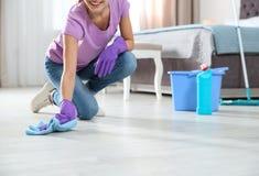 年轻女人与旧布的洗涤物地板和洗涤剂在卧室,特写镜头 库存照片