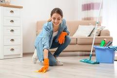 年轻女人与旧布的洗涤物地板和洗涤剂在客厅 图库摄影