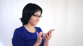 年轻女人为工作使用一个平均智能手机通过互联网 商业和技术 股票录像