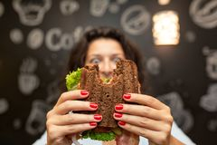 年轻女人举行被咬住的三明治特写镜头滑稽的被弄脏的protrait由她的两只手的 三明治在焦点 可能 库存照片