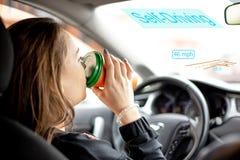 年轻女人乘坐汽车用自治驾驶的方式和饮料咖啡 免版税图库摄影