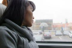 年轻女人乘驾在公共汽车上 免版税库存照片