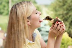 年轻女人亲吻一点鸭子 鸭子采女孩舌头 免版税库存图片