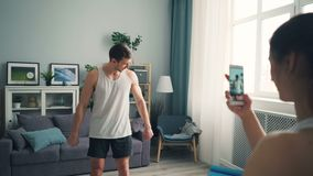年轻女人使用智能手机照相机的英俊的男性爱好健美者录音录影  股票视频