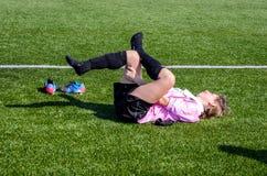 年轻女人做舒展在足球比赛以后 库存图片