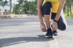 年轻女人停下来栓串,当跑在体育场,健身栓鞋带的妇女赛跑者内在赛跑前时 免版税库存照片