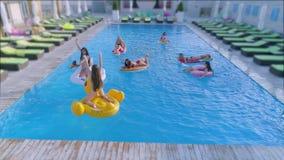 年轻女人公司游泳衣的在可膨胀的圈子和床垫在水池游泳并且放松在昂贵的手段 股票视频