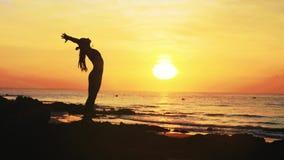 年轻女人剪影做着在海洋海滩的瑜伽锻炼在日落 股票视频