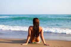 年轻女人剪影海滩的 坐在海边前面的少妇 放松在海滩的比基尼泳装的女孩 妇女 免版税图库摄影