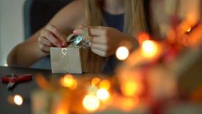 年轻女人包装的礼物 在与红色和金丝带的工艺纸包裹的礼物圣诞节或新年 股票视频