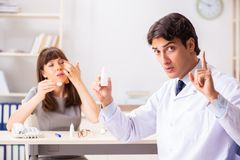 年轻女人参观的男性医生眼科医生在医院 免版税图库摄影